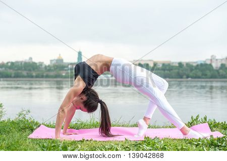 Eoman doing stretching exercise in nature. Backbend
