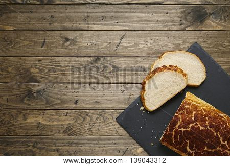 A loaf and slices of crusty white tiger bread on a rustic slate and wooden table top