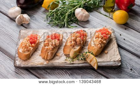 Sandwiches and piece of lemon. Chopped tomatoes and fish meat. Bruschetta with salmon. Delicious italian appetizer.