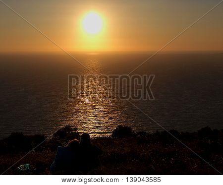 Greek sunset. island of Zakynthos, Greece - June 16, 2014 Man and woman admiring the sunset on the Greek island of Zakynthos