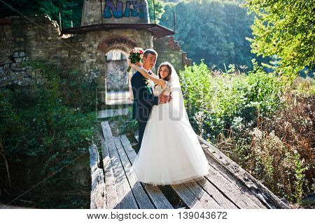 Wedding Couple Stay On Old Wooden Bridge