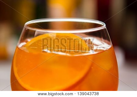 Glass with orange beverage. Slice of fresh orange. Aperol spritz served at nightclub. Alcohol and soda water.