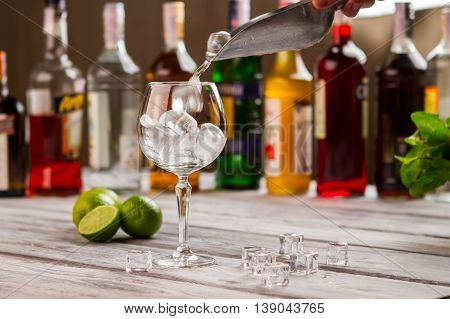 Scoop with ice over wineglass. Limes near ice cubes. Preparing a cool drink. You need to freshen up.