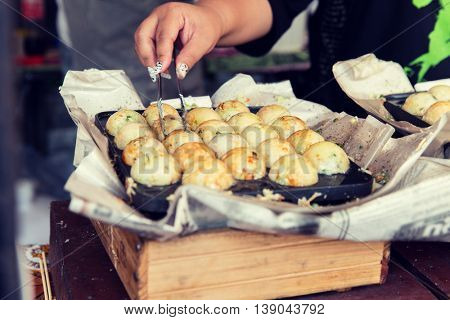 cooking, asian kitchen, sale and food concept - close up of cook hands with meatballs at street market