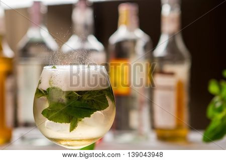 Drink with mint in glass. Beverage with foam. Hugo cocktail served at pub. Champagne and sweet syrup.