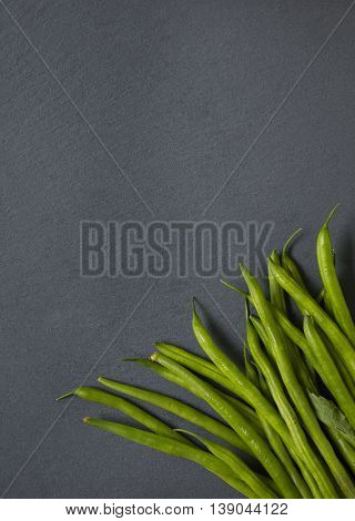 Green beans on a slate background forming a vegetable themed page border