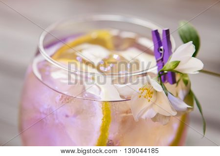Cocktail decorated with white flower. Glass with transparent liquid. Special recipe of tom collins. Celebrate and have fun.