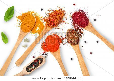 Composition of different spices in wooden spoons on light background