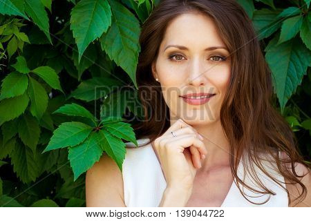 Closeup portrait of beautiful brunette woman outdoors with green enviroment