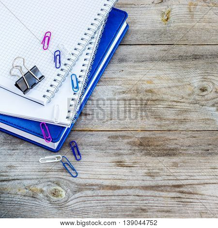 Still life, business, education concept. Stack of notebooks on a rustic wooden table. Selective focus, copy space, school background, top view