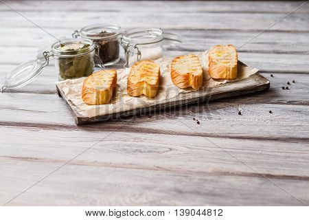 Sliced baguette on board. Jar full of bay leaves. Preparation of dietary meal. Delicious and low in calories.