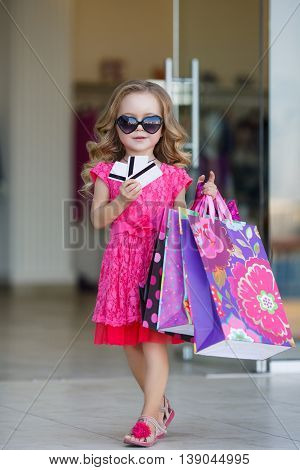 Beautiful little girl with blond long curly hair,sun glasses with glass in the form of hearts,in a pink dress with a bunch of colored shopping bags,posing standing near the entrance to the supermarket with credit cards