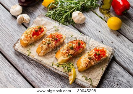 Sliced baguette with fish meat. Garlic and green herb. Freshly cooked meal on table. Recipe of salmon bruschetta.