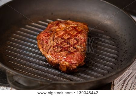 Grilled meat on black pan. Piece of cooked meat. Juicy steak from beef. Lots of protein.