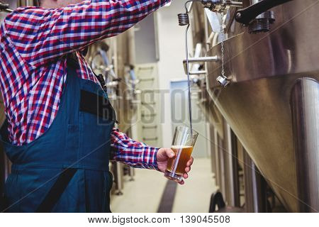 Midsection of manufacturer filling beer into glass from storage tank at brewery