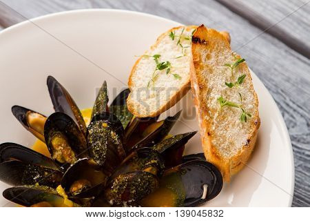 Cooked mussels on plate. Sliced bread and herb. Dish from french cuisine. Seafood in wine sauce.