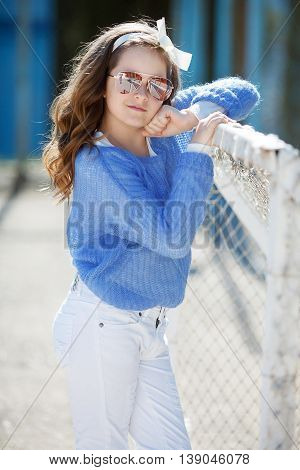 Cute teen girl, caucasian appearance, brunette with long curly hair, wearing sun glasses, wearing a blue jacket, color white ribbon tied around, spending time in the village on the football field at spring outdoor.