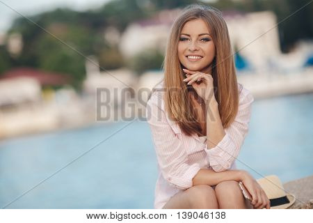 Portrait of a beautiful woman,brunette with long straight hair and gray eyes,a nice smile and beautiful white teeth,dressed in a white shirt resting on the shore of the blue ocean in the summer in the fresh air