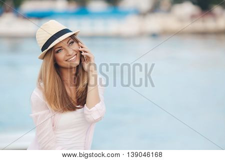 Girl in a beige hat with a black stripe,a beautiful smile,gray eyes,white straight teeth,long blonde straight hair,wearing a light pink and white stripes shirt, talking on mobile phone sitting on the embankment near the blue ocean
