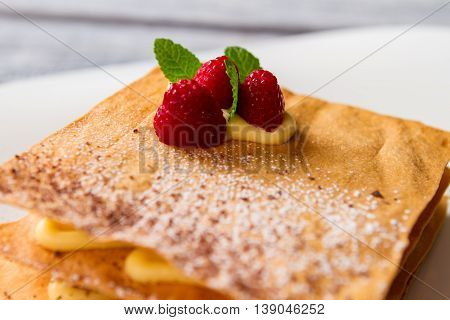 Pastry with mint leaves. Yellow custard and red berries. Delicious millefeuille with raspberries. Dessert in french restaurant.