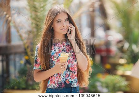 Summer portrait of a very beautiful young woman with gray eyes and long straight brown hair,a nice smile,wearing jewelry,wearing blue shorts and a colored shirt,right hand holds an ice cream cone,talking on the phone in summer Park