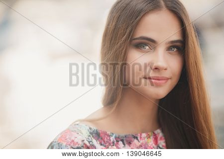 Closeup portrait of young beautiful woman with grey eyes,brunette with long straight hair,light makeup and cute smile,dressed in a colorful blouse,posing in the summer outdoors