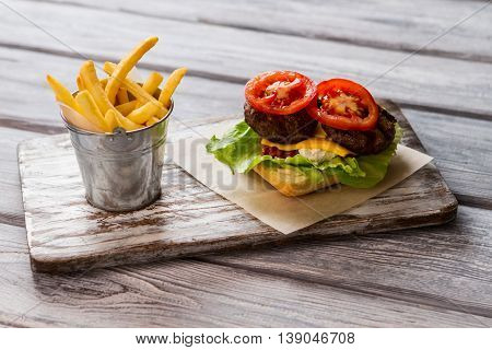 Bucket filled with fries. Tomato slice and grilled meat. Ingredients for tasty hamburger. You should taste this.