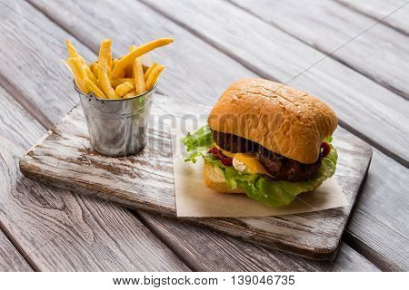 Burger and bucket of fries. Hamburger on piece of paper. Delicious fast food meal. Traditional recipe of beefburger.