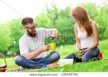 Young couple on a picnic in a park. Man pouring hot coffee from a thermos bottle