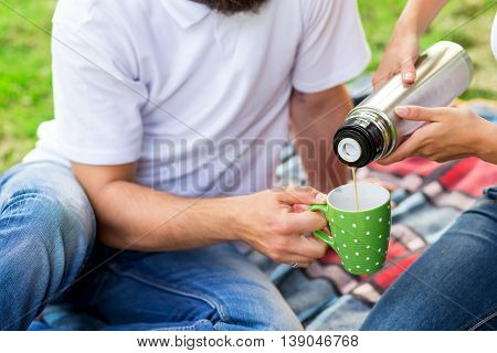 Young couple on a picnic in a park. Girl pouring hot coffee from a thermos bottle. Focus on the cup and thermos bottle