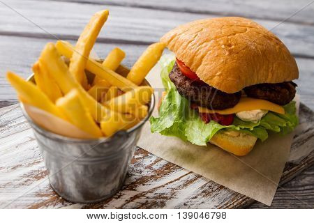 French fries and hamburger. Cheese and lettuce. Typical fast food meal. Danger for your health.