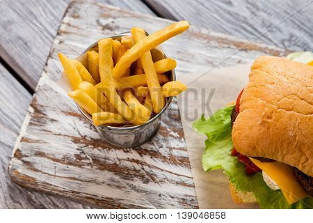 Hamburger and bucket with fries. Top view of french fries. Tasty meal in diner. So fresh and crispy.