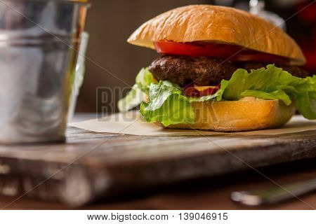 Hamburger with lettuce leaves. Ketchup and grilled meat. Relax and eat. Juicy beef and garlic sauce.