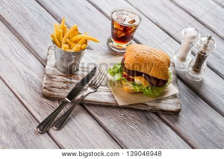 Hamburger and bucket of fries. Glass with cola. Delicious snack in american cafe. Chilled beverage with sweet taste.