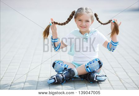 Blonde little girl with two long pigtails wearing a white t-shirt and blue shorts,wearing knee pads and protection on elbows blue,spends time alone in a city Park, roller skating black and blue in the summer