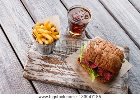 Glass of cola and fries. Sandwich with brown bread. Appetizing meal in roadside diner. Stay full of energy.