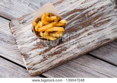French fries in a bucket. Top view of yellow fries. Dish high in fats. Example of processed food.