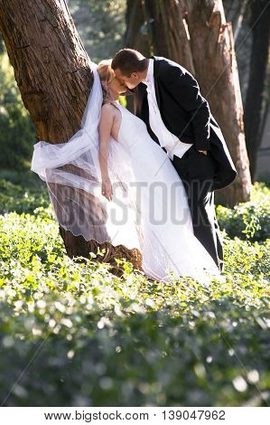 Newlywed couple in a forest dancing together.