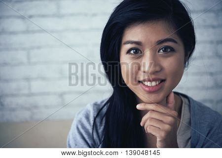 Face of attractive mixed-race woman smiling and looking at camera