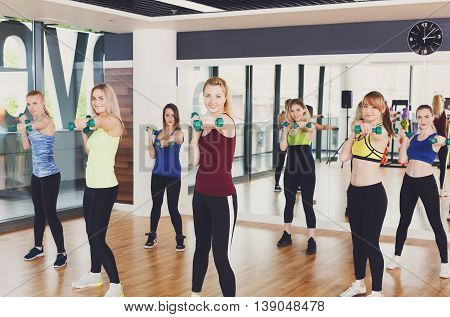 Group of young women in fitness club making exercises with dumbbels. Healthy lifestyle, slim sporty girls at aerobics training.