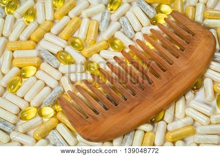 Wooden hairbrush on capsules and pills as a background. Medical hair care concept, closeup, top view
