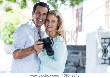 Portrait of happy couple with camera standing on street in city