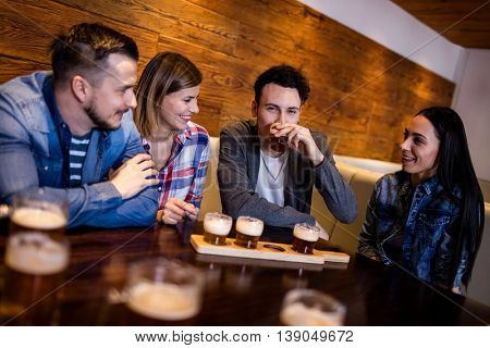 Happy friends having beer at table in restaurant