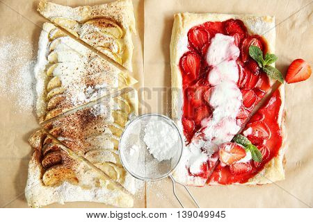 Sliced strawberry and apple desserts with sieve on parchment background