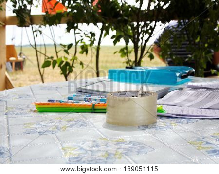 on the table under a canopy of branches lie tape and stationery