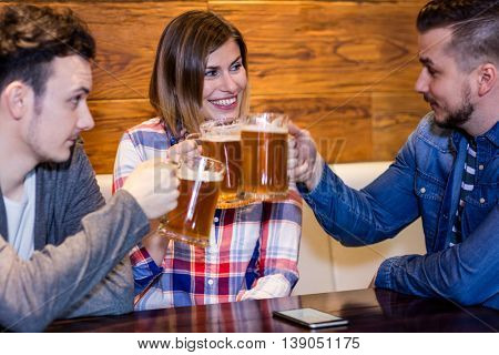 Smiling friends toasting beer at restaurant