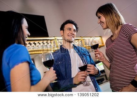 Low angle view of young friends with wineglass at restaurant