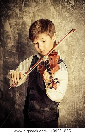 Freckled nine year old boy playing the violin. Musical education. Inspiration.