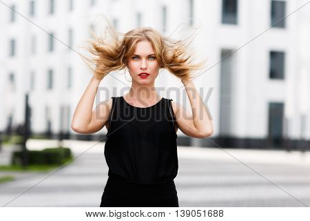 Portrait of young cute lady with shaggy blond hair in wind outdoors