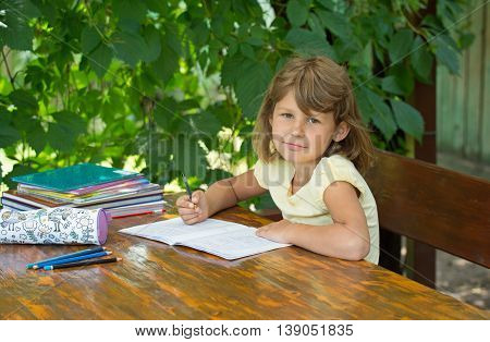 cute girl making lessonsGirl makes lessons sitting at a table in the garden